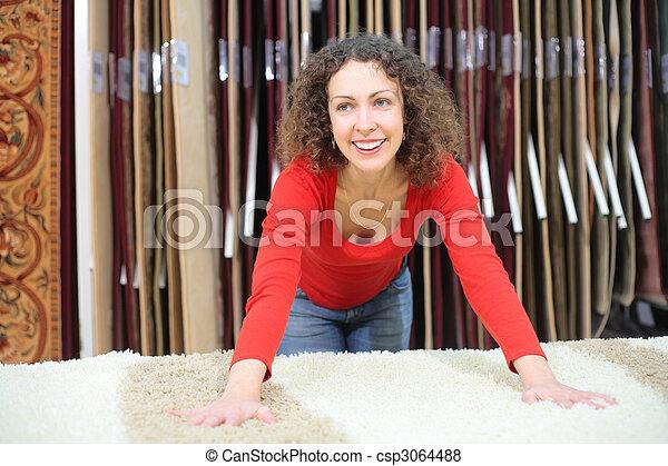 Una joven en la tienda con una alfombra peluda - csp3064488