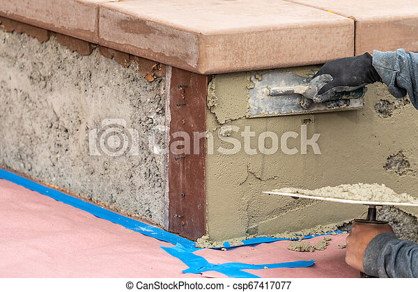 Tile Worker Applying Cement with Trowel at Pool Construction Site - csp67417077