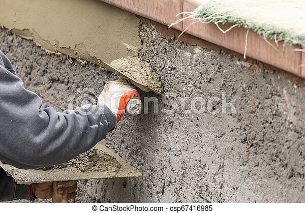 Tile Worker Applying Cement with Trowel at Pool Construction Site - csp67416985