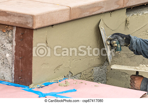 Tile Worker Applying Cement with Trowel at Pool Construction Site - csp67417080