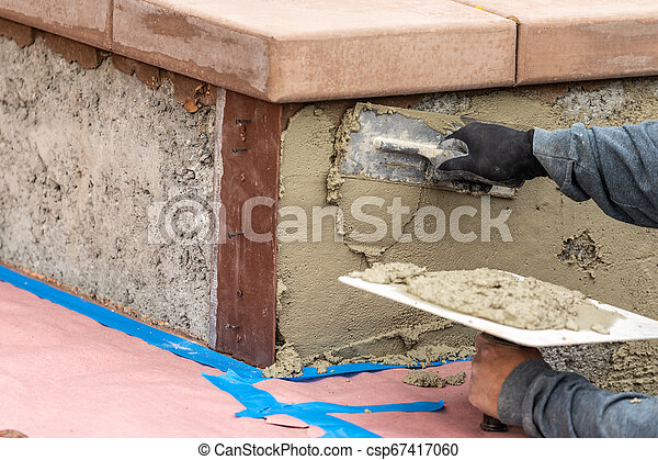 Tile Worker Applying Cement with Trowel at Pool Construction Site - csp67417060