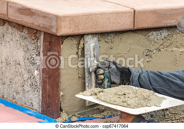 Tile Worker Applying Cement with Trowel at Pool Construction Site - csp67417064