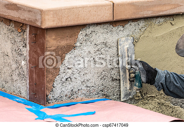 Tile Worker Applying Cement with Trowel at Pool Construction Site - csp67417049