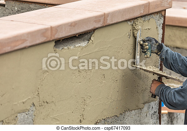 Tile Worker Applying Cement with Trowel at Pool Construction Site - csp67417093