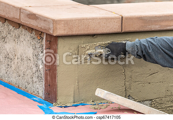 Tile Worker Applying Cement with Trowel at Pool Construction Site - csp67417105