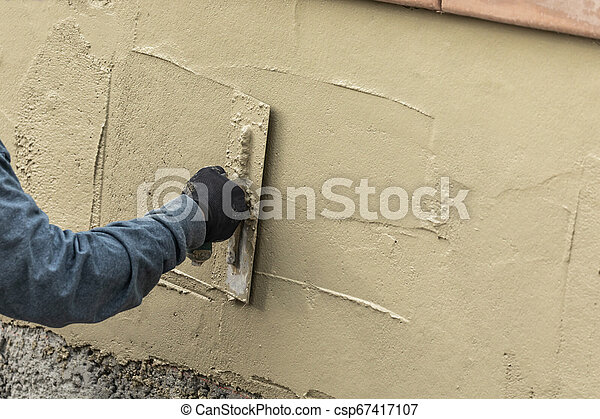 Tile Worker Applying Cement with Trowel at Pool Construction Site - csp67417107