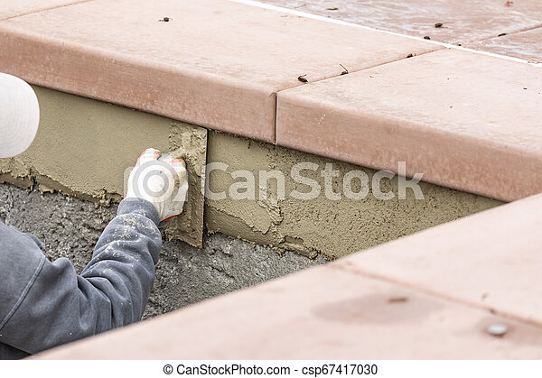Tile Worker Applying Cement with Trowel at Pool Construction Site - csp67417030
