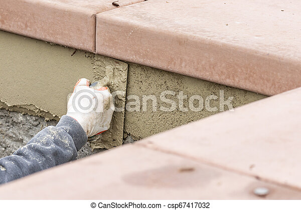 Tile Worker Applying Cement with Trowel at Pool Construction Site - csp67417032