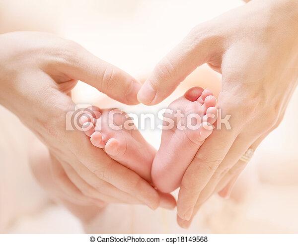 Tiny Newborn Baby's feet on female Heart Shaped hands closeup - csp18149568