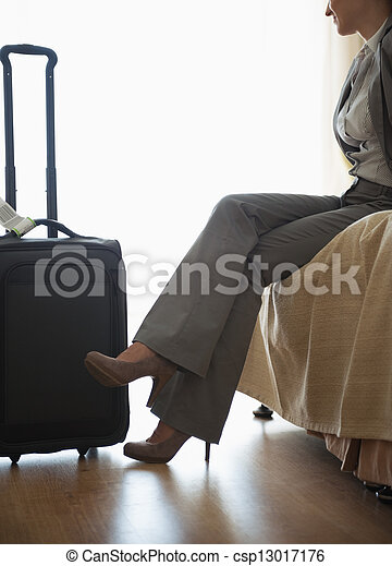 Tired business woman sitting on bed in hotel room after trip - csp13017176