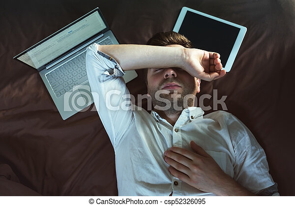 Tired Caucasian Young Man In White Shirt Sleeping And Keeping One Hand Above Head Lying On Bed Near Laptop He Is Tired Of