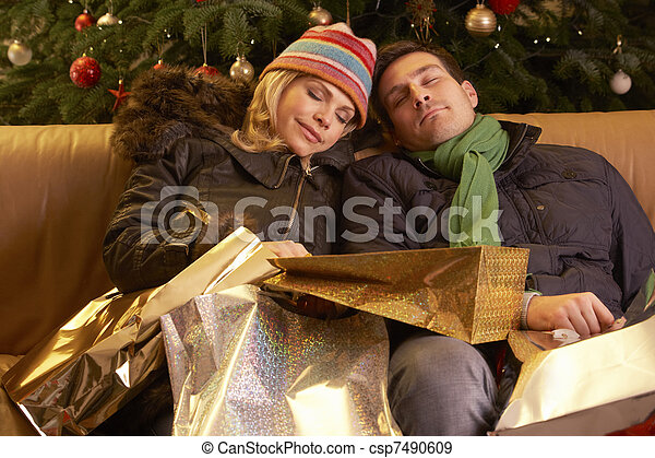 Tired Couple Returning After Christmas Shopping Trip - csp7490609