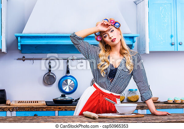 Tired housewife cooking in kitchen. Beautiful tired ...
