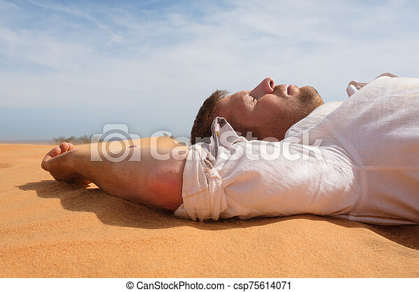 Tired man lying on the sand in a desert. - csp75614071