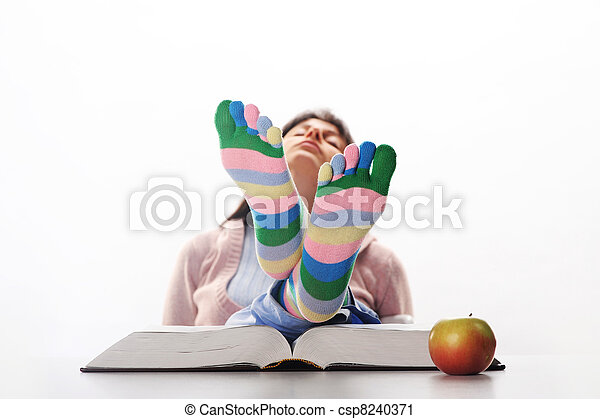 Tired of studies,  student relaxing  with his feet up on his desk, similar pictures on my portfolio - csp8240371