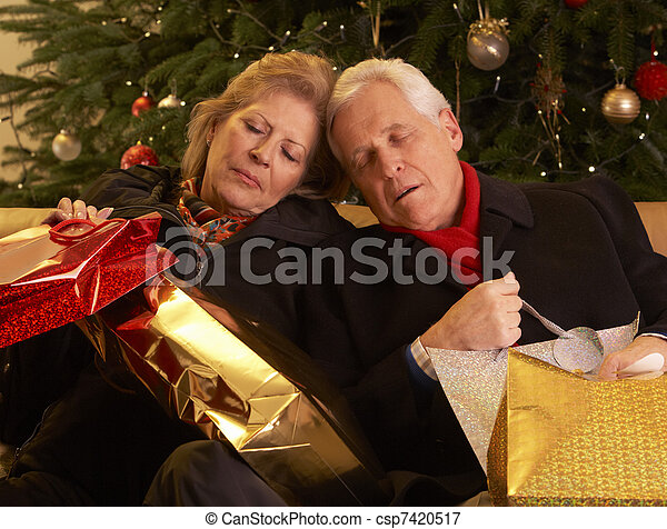 Tired Senior Couple Returning After Christmas Shopping Trip - csp7420517
