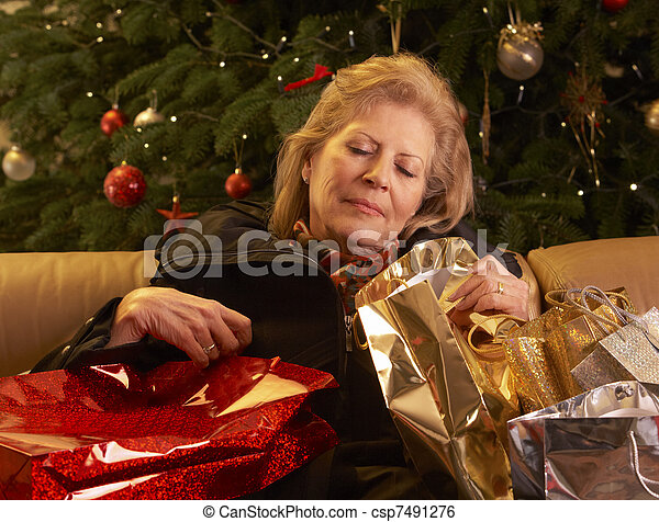 Tired Senior Woman Returning After Christmas Shopping Trip - csp7491276