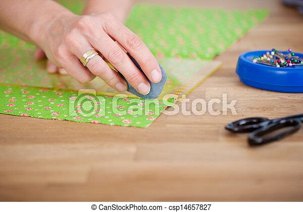 Las manos del diseñador marcan tela con tiza en la tela - csp14657827