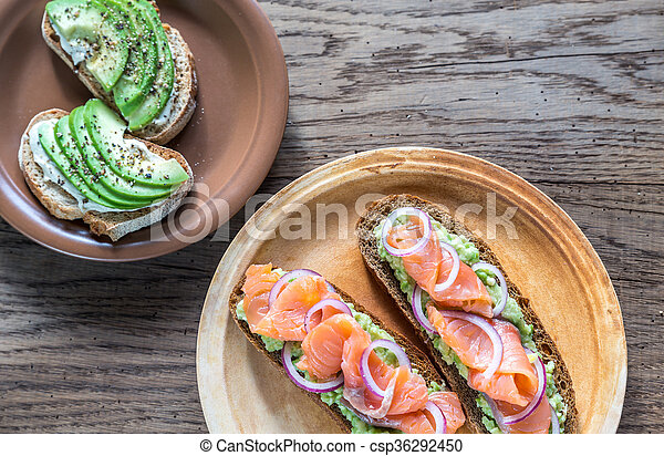 Toasts with avocado and different toppings - csp36292450