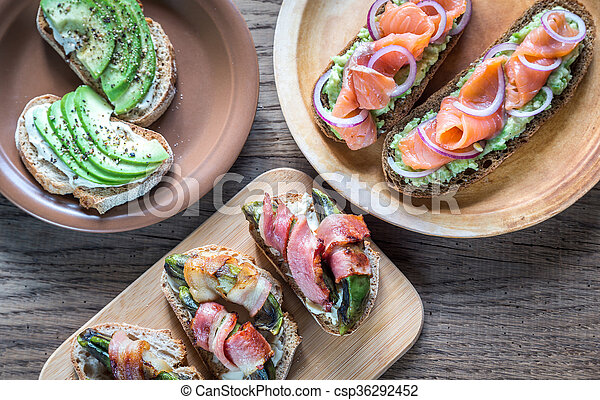 Toasts with avocado and different toppings - csp36292452