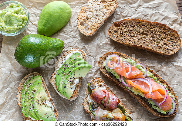 Toasts with avocado and different toppings - csp36292423
