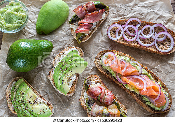 Toasts with avocado and different toppings - csp36292428
