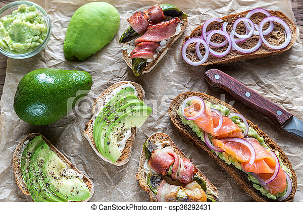 Toasts with avocado and different toppings - csp36292431