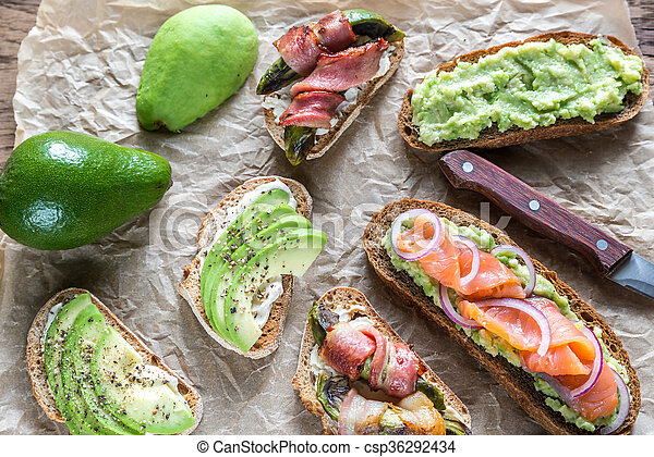 Toasts with avocado and different toppings - csp36292434