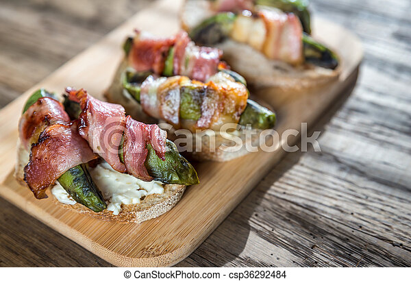 Toasts with cream cheese and avocado wrapped in bacon - csp36292484