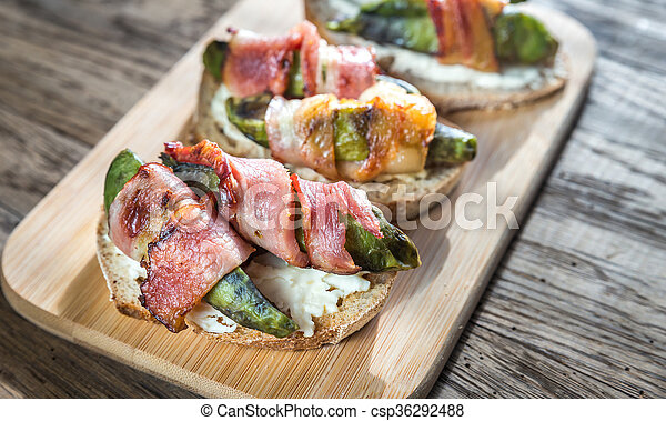 Toasts with cream cheese and avocado wrapped in bacon - csp36292488