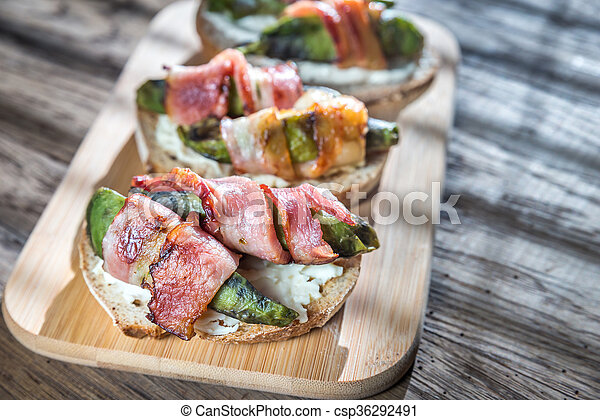 Toasts with cream cheese and avocado wrapped in bacon - csp36292491