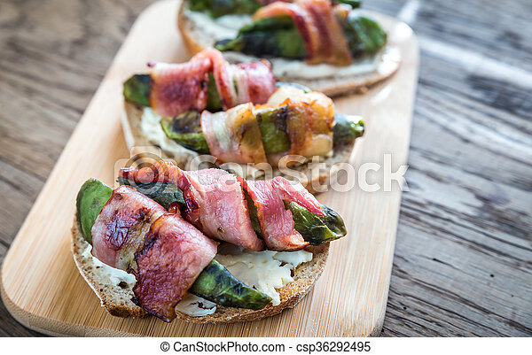 Toasts with cream cheese and avocado wrapped in bacon - csp36292495