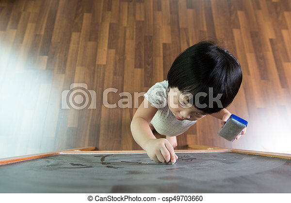 Toddler drawing on chalkboard - csp49703660