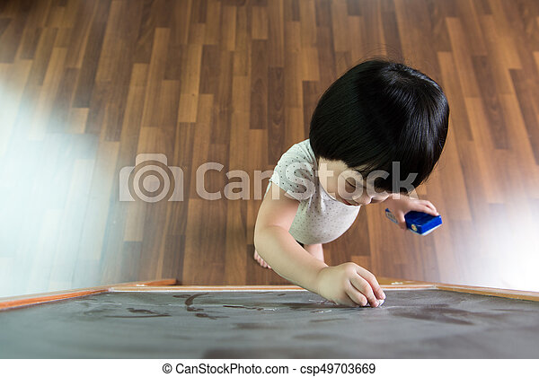Toddler drawing on chalkboard - csp49703669