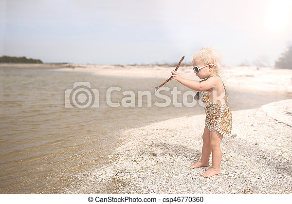 Toddler Girl Playing on Beach Throwing Sticks in the Water - csp46770360