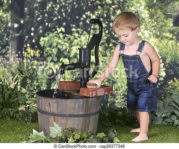 Toddler Scrubbing Bricks by the Water Pump - csp29377346
