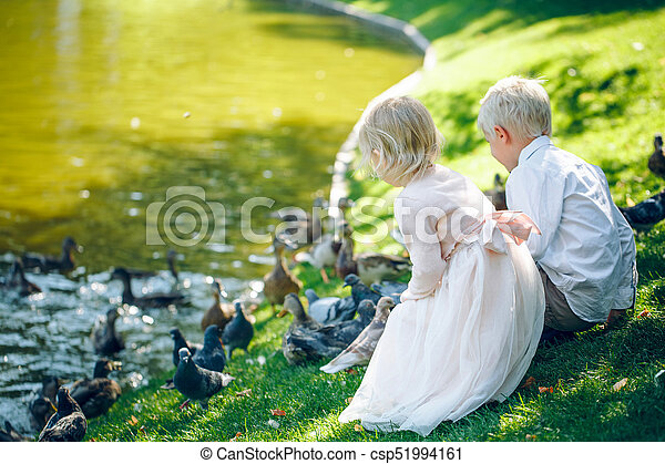 Toddlers boy and girl sitting on grass near the lake and fed the pigeons with bread - csp51994161