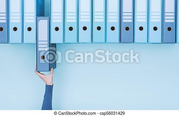Trabajador de oficina tomando una carpeta en el archivo - csp56031429
