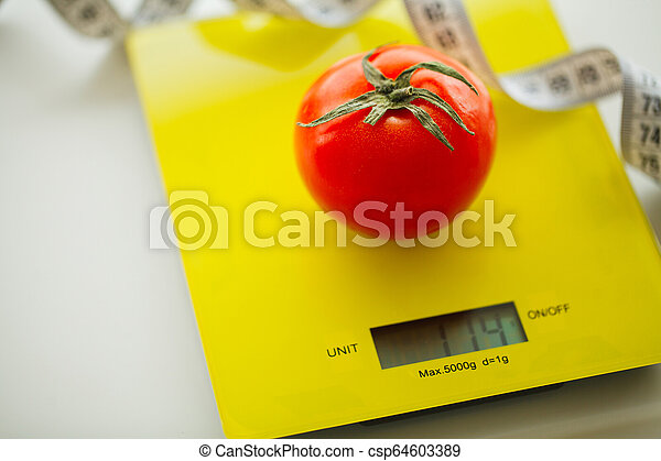 Dieta. Tomate con cinta métrica en la escala de peso - csp64603389