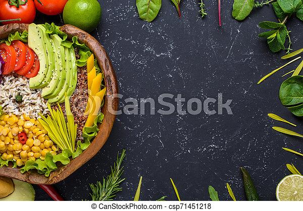 Tazón de súper comida vegetariana saludable con quinoa, arroz silvestre, garbanzos, tomates, aguacate, verduras, repollo, lechuga en fondo negro de piedra, vista de primera con espacio de copia. Comida y salud - csp71451218
