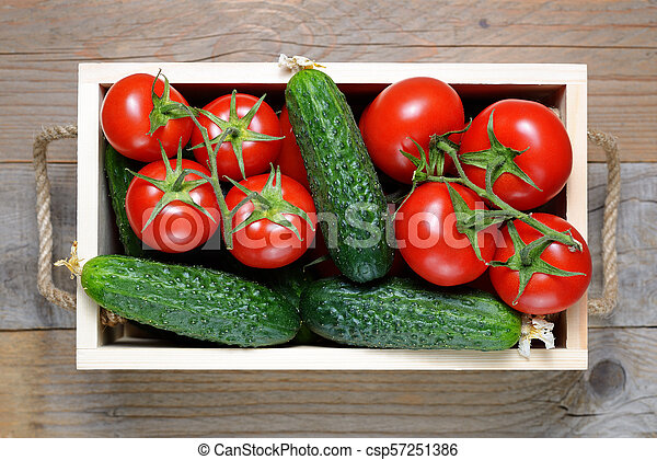 Tomatoes and cucumbers in wooden box close-up - csp57251386