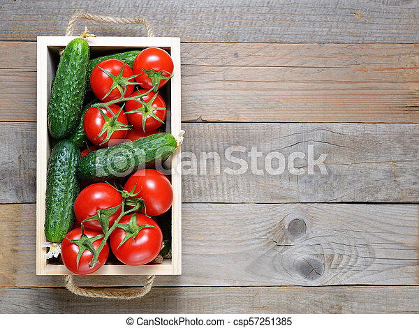 Tomatoes and cucumbers in wooden box top view - csp57251385