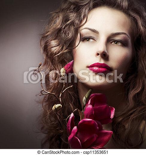 Una mujer de moda con magnolia flores de primavera. Sepia toned - csp11353651