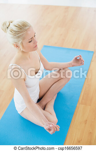 Toned woman sitting in lotus pose a - csp16656597