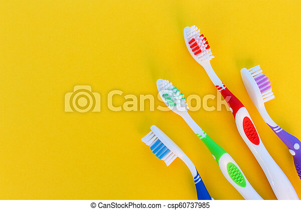 Toothbrushes on yellow background. Top view. - csp60737985