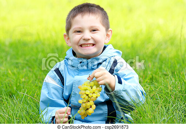 Toothy smiling boy with grapes - csp2691873