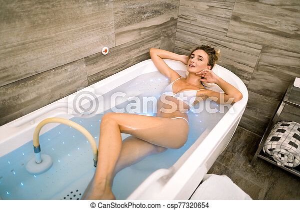 Top Angle View Of Young Attractive Smiling Woman Looking At Camera And Lying In Hot Water In Bathtub With Hydromassage In Spa Canstock