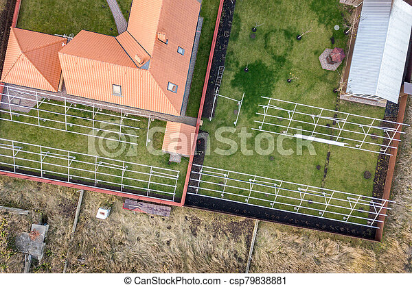 Top down aerial view of a private house with red tiled roof and frame structure prepared for installation of solar panels. - csp79838881