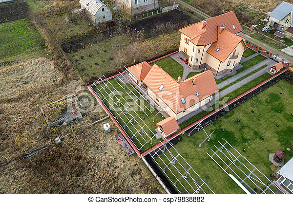 Top down aerial view of a private house with red tiled roof and frame structure prepared for installation of solar panels. - csp79838882
