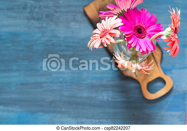 Top shot of pink flowers on a blue background and on a small table. - csp82242207